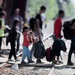 a migrant group crosses train tracks