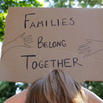 A person holds up a sign that says families belong together