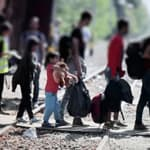 a group of migrants and children cross train tracks