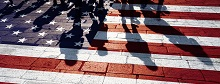 Decorative image of an American flag painted on bricks with shadows of people on it